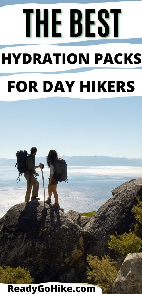 Male and female hiker looking out over water with text overlay The Best Hydration Packs for Day Hikers